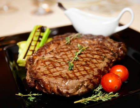 rib eye: Rib eye steak served on black plate with sauce, herbs and grilled vegetables