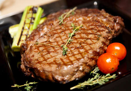 Rib eye steak served on black plate with herbs and grilled vegetables Stock Photo