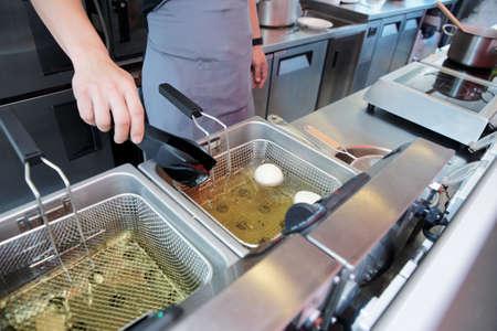 negocios comida: Chef de cocina el plato en una freidora de aceite de cocina de restaurante en ebullici�n  Foto de archivo