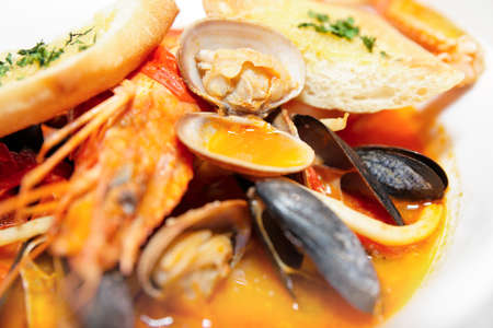 Seafood soup of langoustines, calamari, clams, mussels etc photo