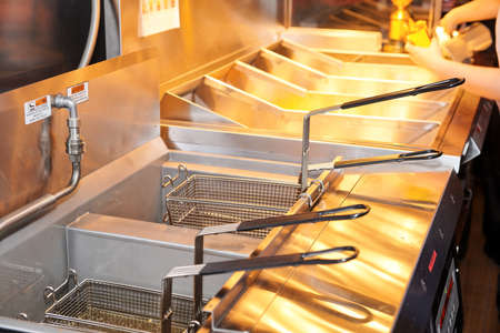 Deep fryer with boiling oil on restaurant kitchen  Stock Photo