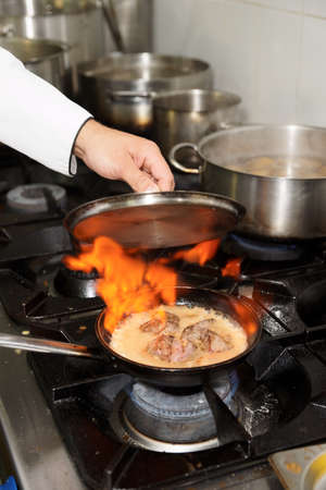 Chef is making flambe liver on restaurant kitchen