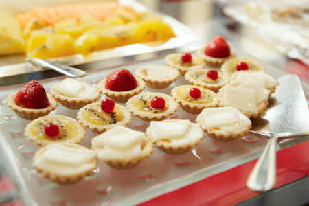 fruit platter: Sweets on banquet table - tartlets with white chocolate and berries