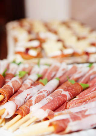 party tray: Snacks on banquet table - prosciutto ham on grissini sticks