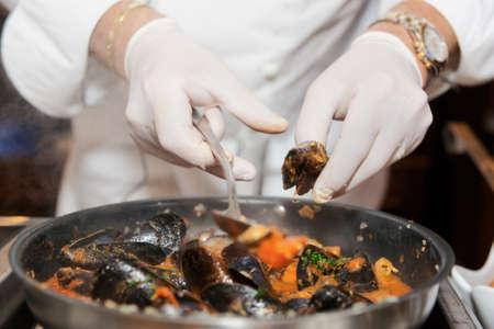 Chef Braten Muscheln auf gewerbliche Küche im Restaurant, close-up auf die Hände Lizenzfreie Bilder
