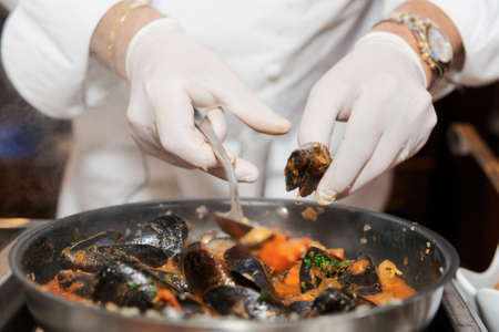 frying: Chef frying mussels on commercial kitchen in restaurant, close-up on hands
