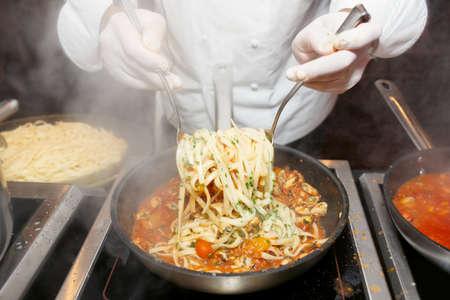 steel pan: Mejillones con pasta para freír Chef en cocina comercial en el restaurante, en primer plano en las manos