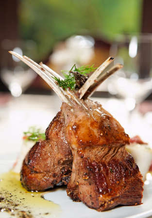 Raw rack of lamb fried with aromatic olive oil, herbs and spices Stock Photo
