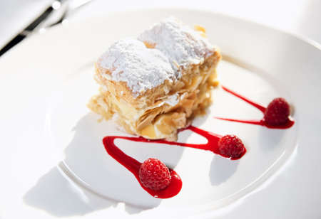 cream puff: Slice of mille-feuille cake with raspberries and sweet sauce on porcelain plate