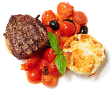 Tasty tenderloin steak with vegetables on plate, isolated photo