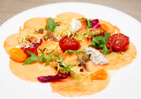 fine fish: Salmon carpaccio with sauce and sun dried tomatos in plate, close-up shot