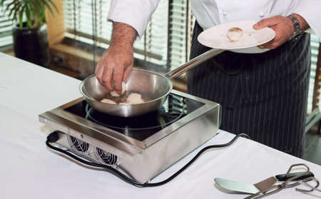 induction: Chef is preparing mussels on induction stove Stock Photo