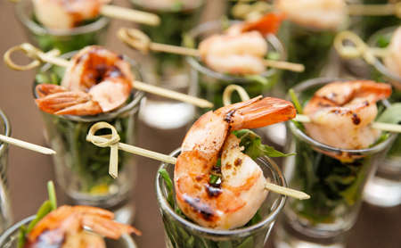 canapes: Tasty appetizer of shrimps and arugula on restaurant table Stock Photo