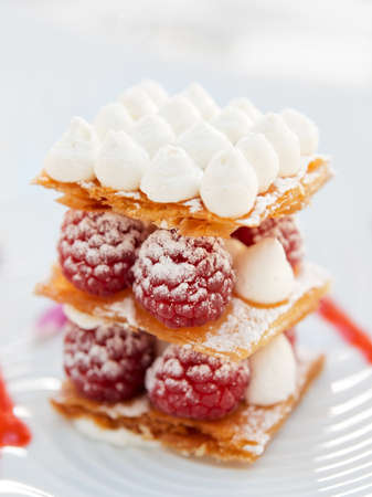 Slice of mille-feuille cake with raspberries and sweet sauce on porcelain plate photo