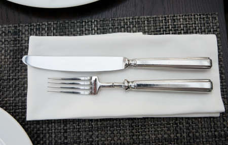 Fork, knife and napkin on table photo