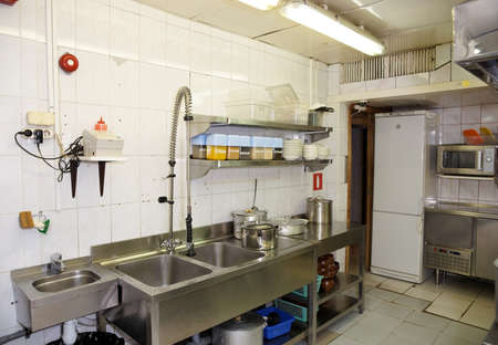 underprivileged: Dish washing room in a restaurant, wide angle