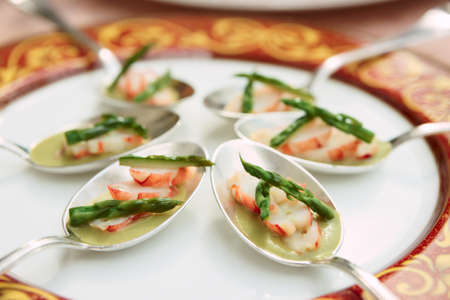 Banquet dish of crab and asparagus in metal spoons photo