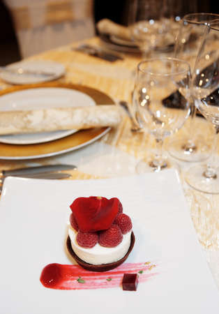 Dessert on plate in restaurant with festive table arrangement in blurred  background photo