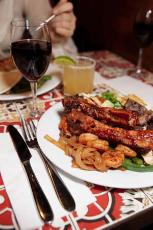 Grilled pork ribs and shrimps with cocktail and wine - perfect dinner photo