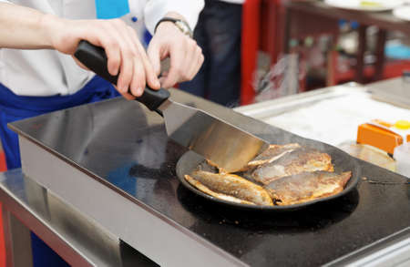 commercial kitchen: Chef frying seabass fillet in pan on commercial kitchen