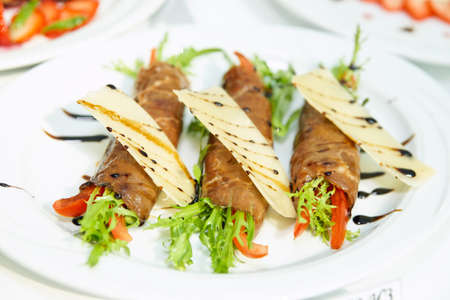 catering food: Meat rolls with arugula, close-up