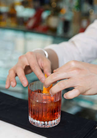 Barman is decorating cocktail with lemon zest photo