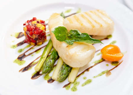 Light grilled fish with salad and asparagus on plate close-up photo