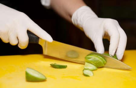 シェフは黄色い板にきゅうりを切っています。 写真素材