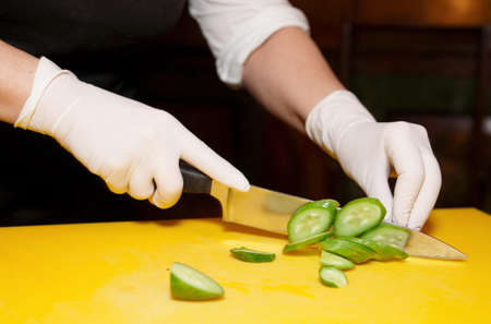 latex glove: Female chef is cutting cucumber on yellow plank