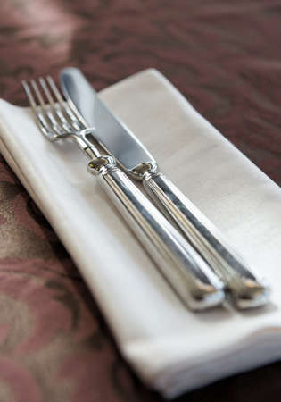 Fork, knife and napkin on restaurant table, shallow focus photo