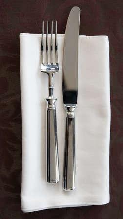 Fork, knife and napkin on restaurant table photo