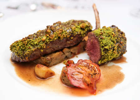 italian cusine: Grilled rack of lamb with mint and pistachio on plate