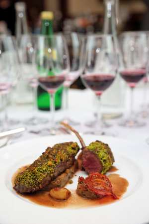 Grilled rack of lamb with mint and pistachio on arranged table photo