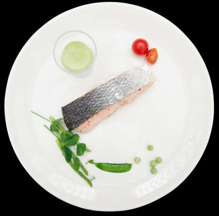 black backgound: Steamed salmon steak with vegetables isolated on black backgound