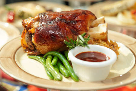 Pork shank with sauce and vegetables on plate Stock Photo