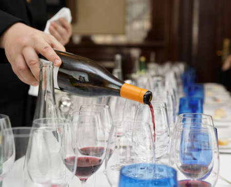 Waiter is pouring wine during a winetasting event Stock Photo - 13970905