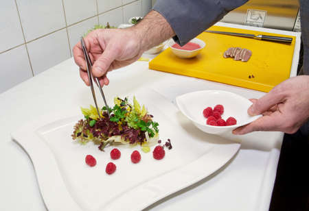 Chef is cooking appetizer of lettuce and raspberries Stock Photo - 13965314