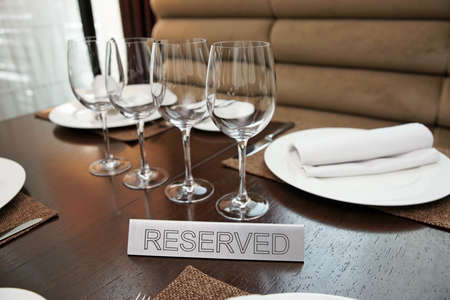 reserved sign: Reserved plate on an arranged restaurant table