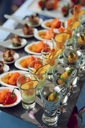 catering service: Spoons and glasses with seafood snacks on banquet table