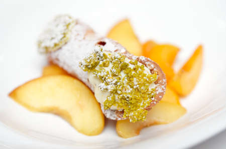 Traditional Sicilian cannoli dessert on plate with pistachio and fruits, close-up photo