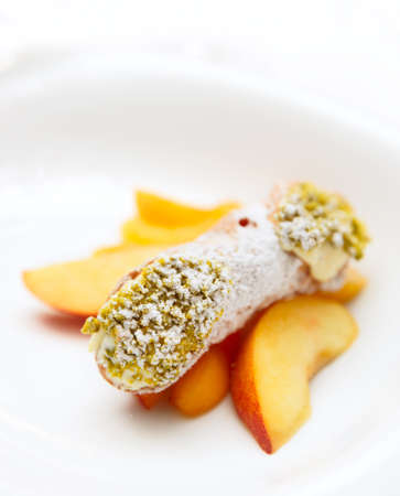 sicilian: Traditional Sicilian cannoli dessert on plate with pistachio and fruits, close-up