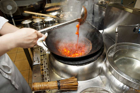 Chef is stirring vegetables with sour sauce in wok at commercial kirchen photo