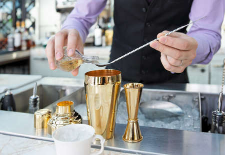 Bartender is adding ingredient in shaker at bar counter photo