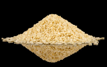 handful: White sesame seeds heap on black reflective surface, isolated on black background
