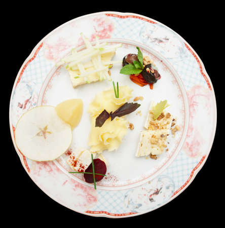 Cheese plate with fruits and nuts isolated on black background photo