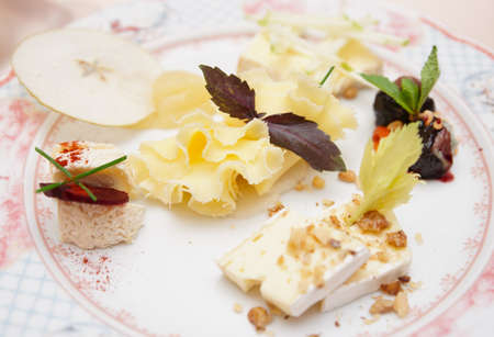 chinoiserie: Cheese assortment with fruits and nuts on porcelain plete