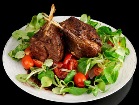 Rare fried rack of lamb isolated on black background photo