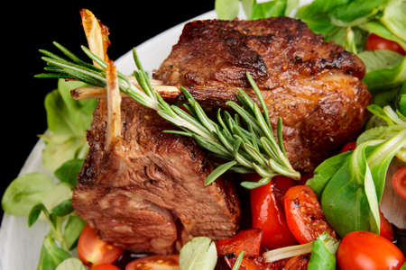 steak dinner: Rare fried rack of lamb isolated on black, close-up Stock Photo