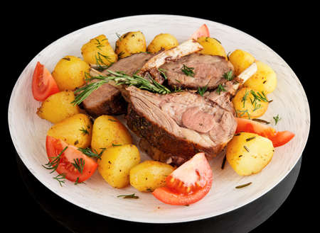 Rack of lamb with fried potatoes isolated on black background photo