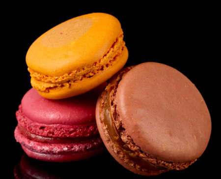 Three colorful macarons isolated on black background photo